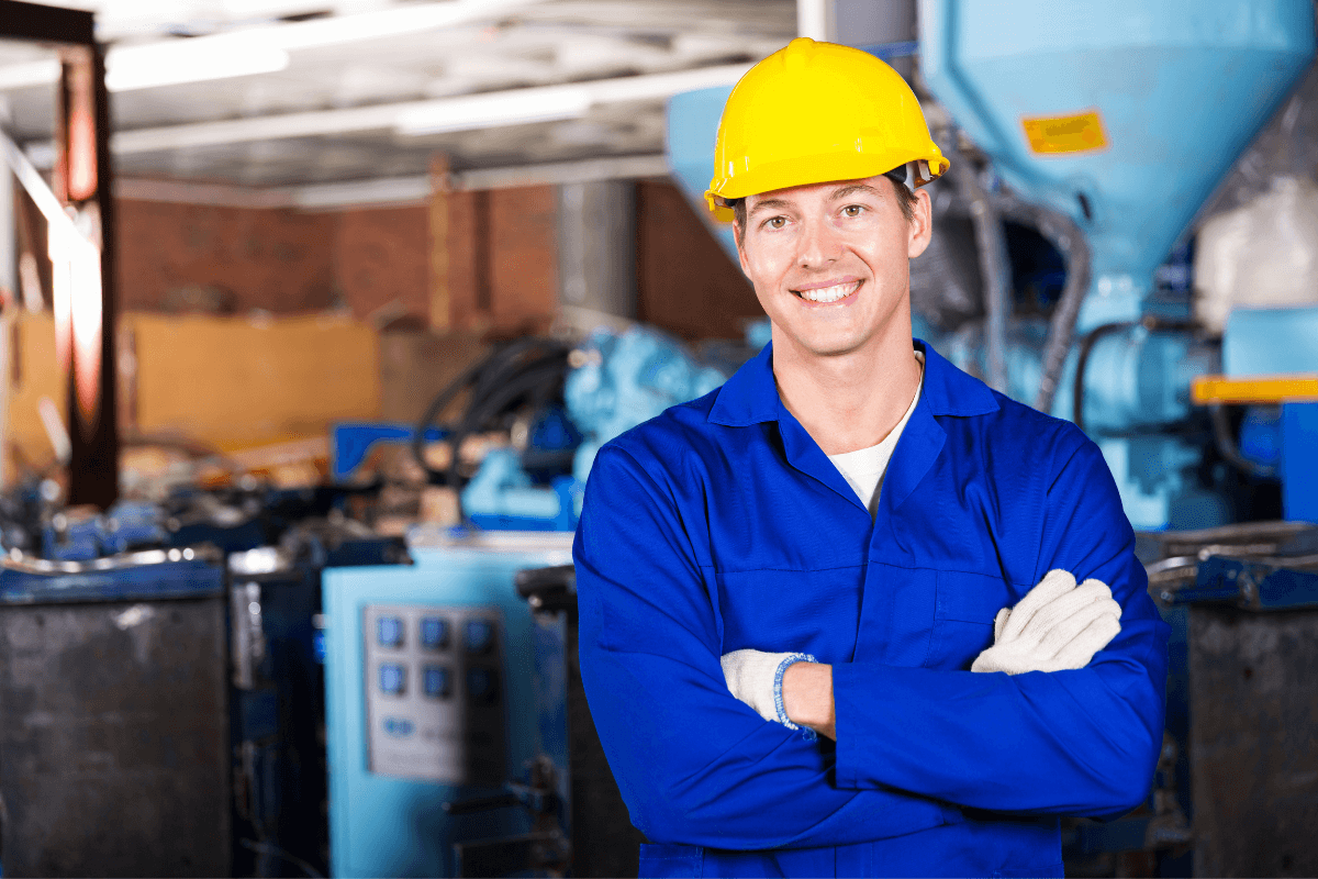 young male worker in yellow hard hat and blue coveralls