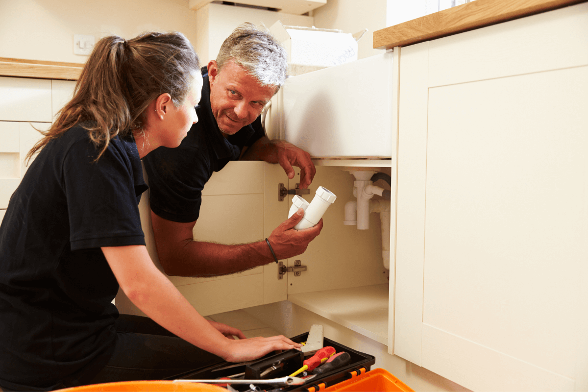 male and female plumbers looking at pipes under a sink