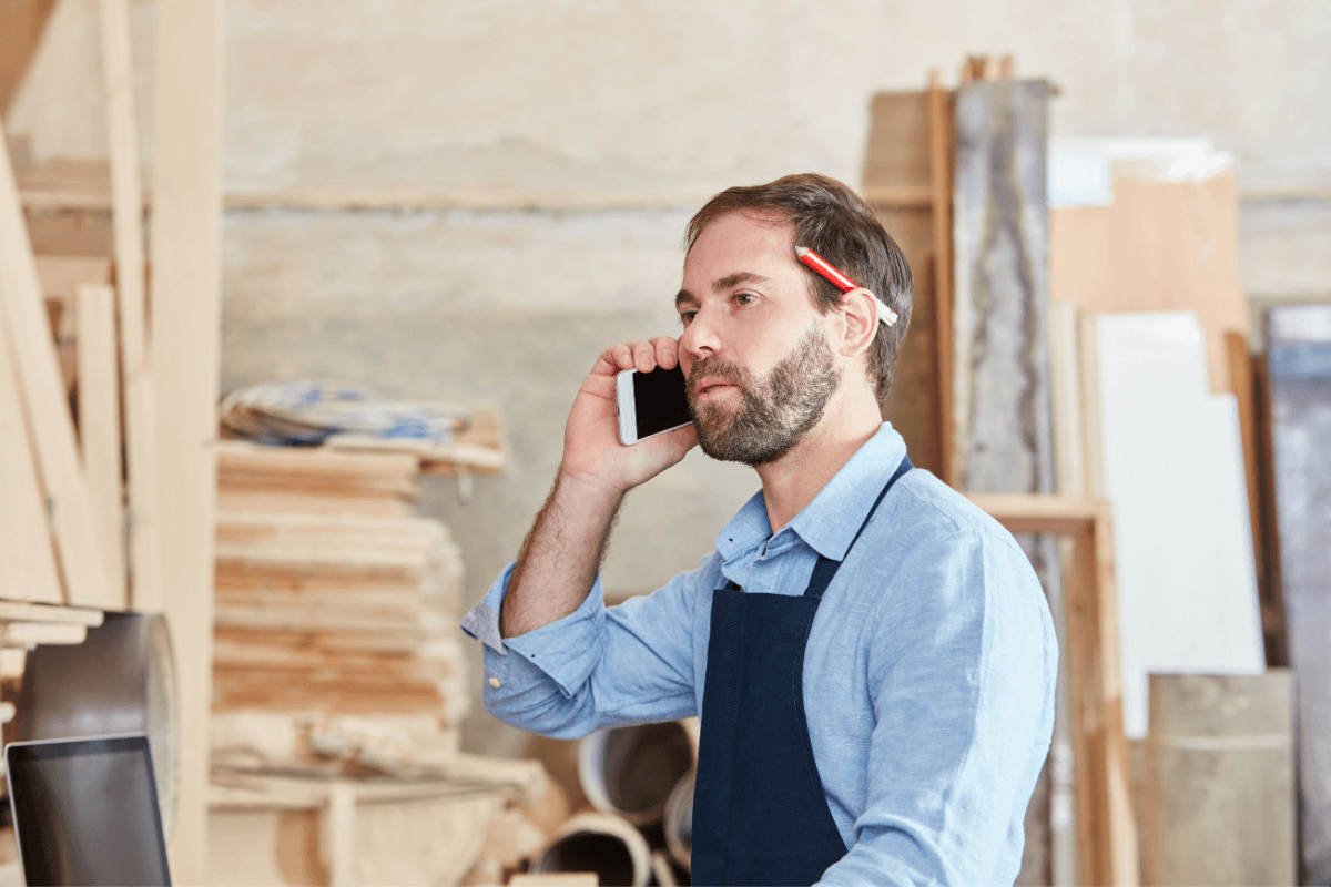 worker at lumber facility talking on a cell phone