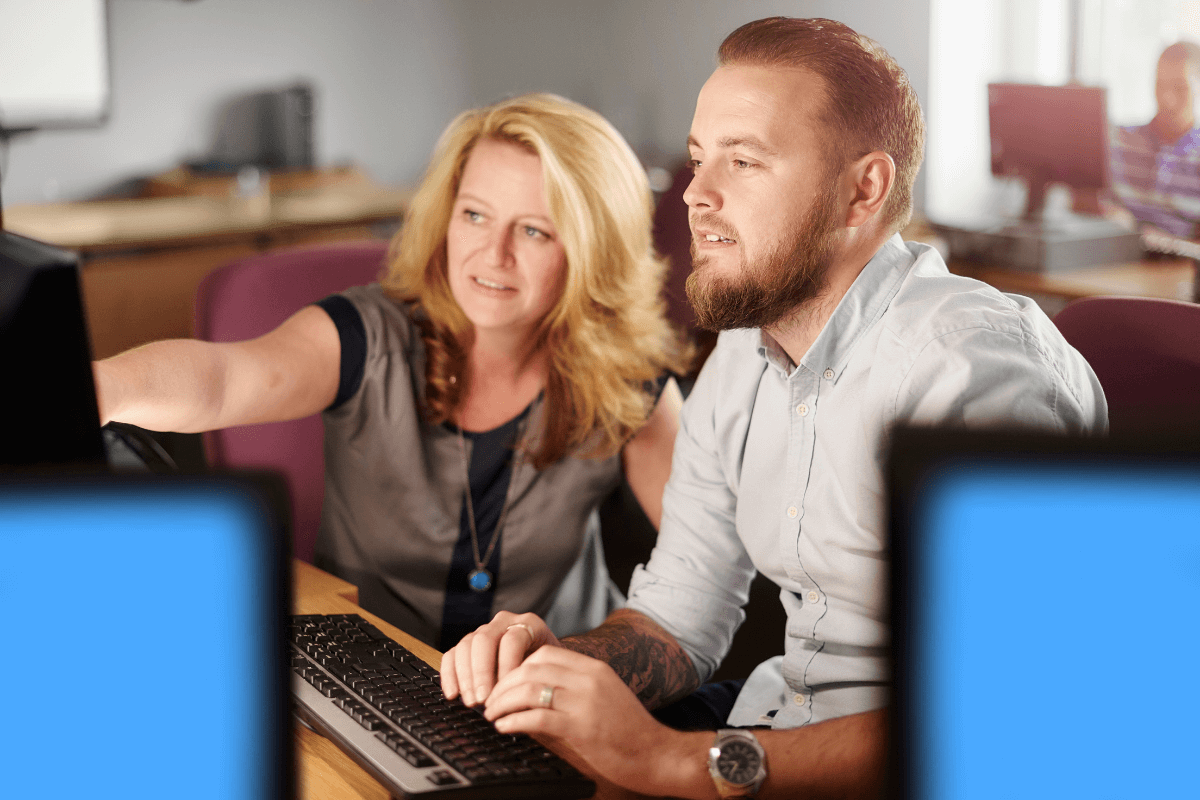 man and woman working together on a computer