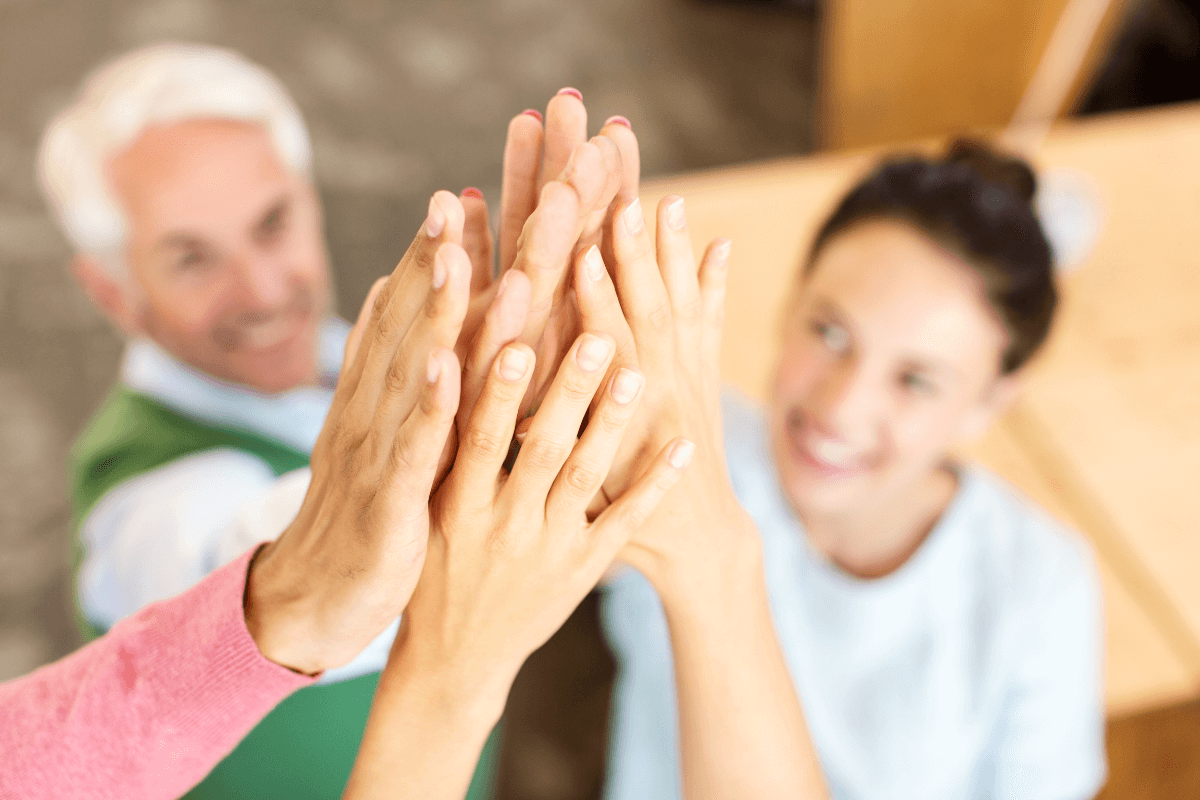 several adults raising their hands to high-five