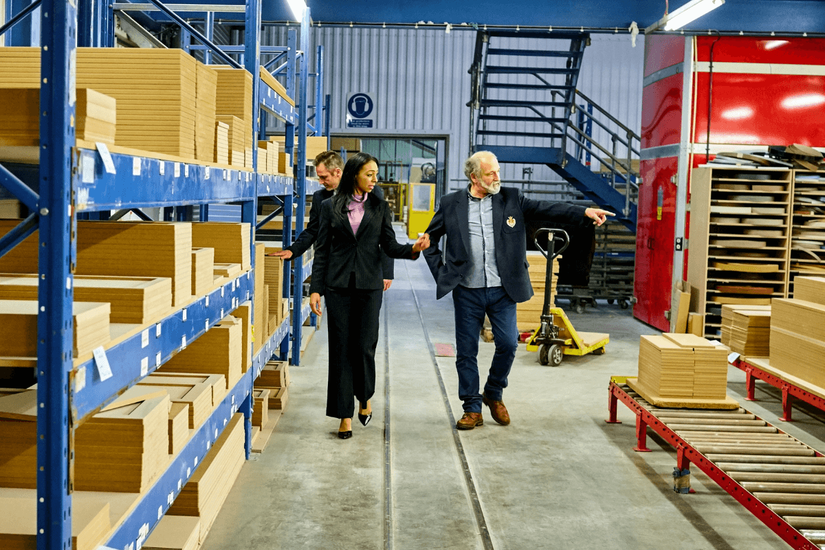 older woman and man walking in a packing facility