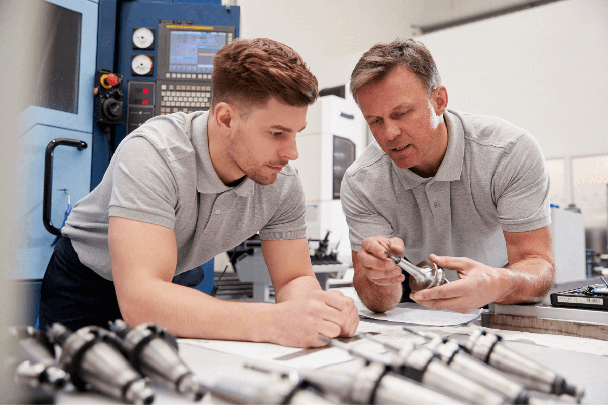 two men in a manufacturing facility looking at parts