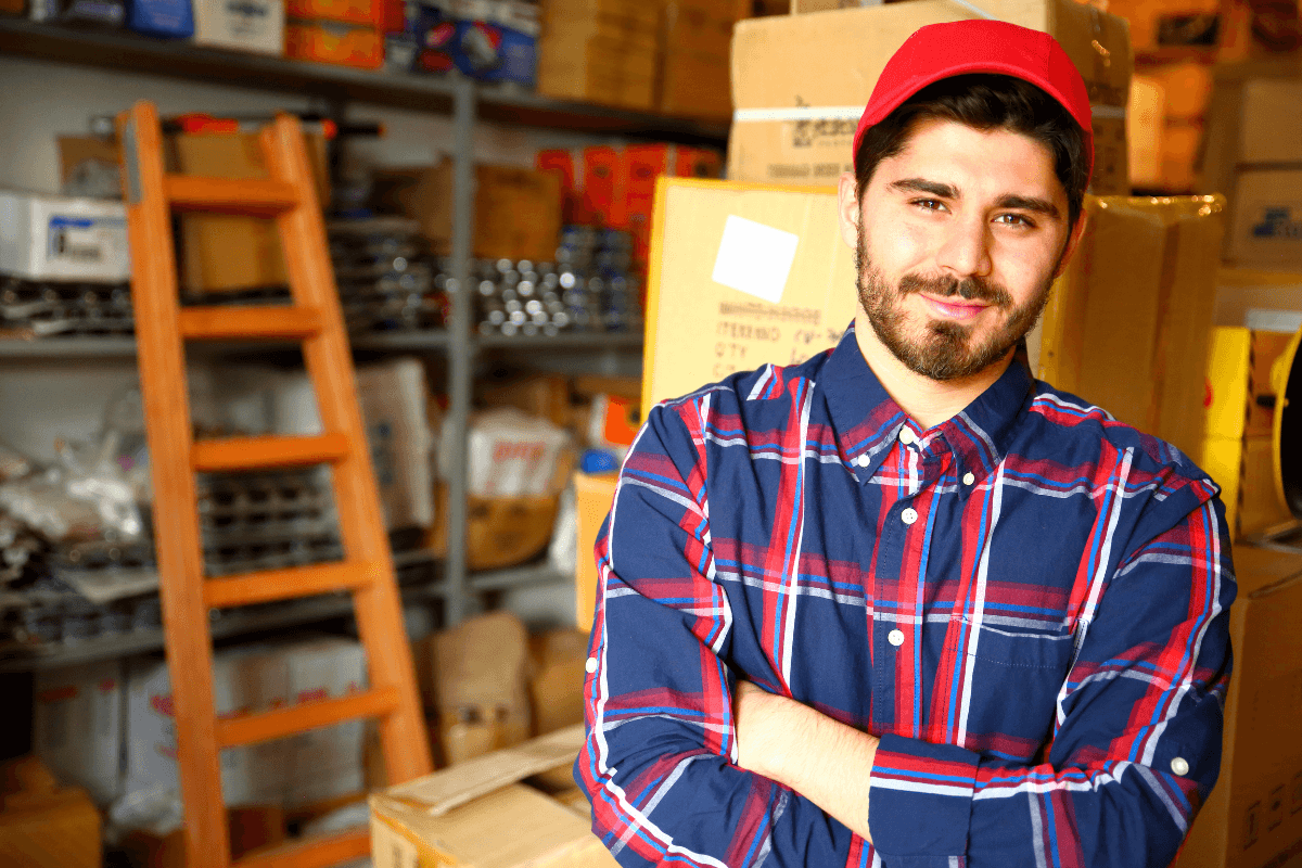young man wearing a plaid shirt standing in front of boxes