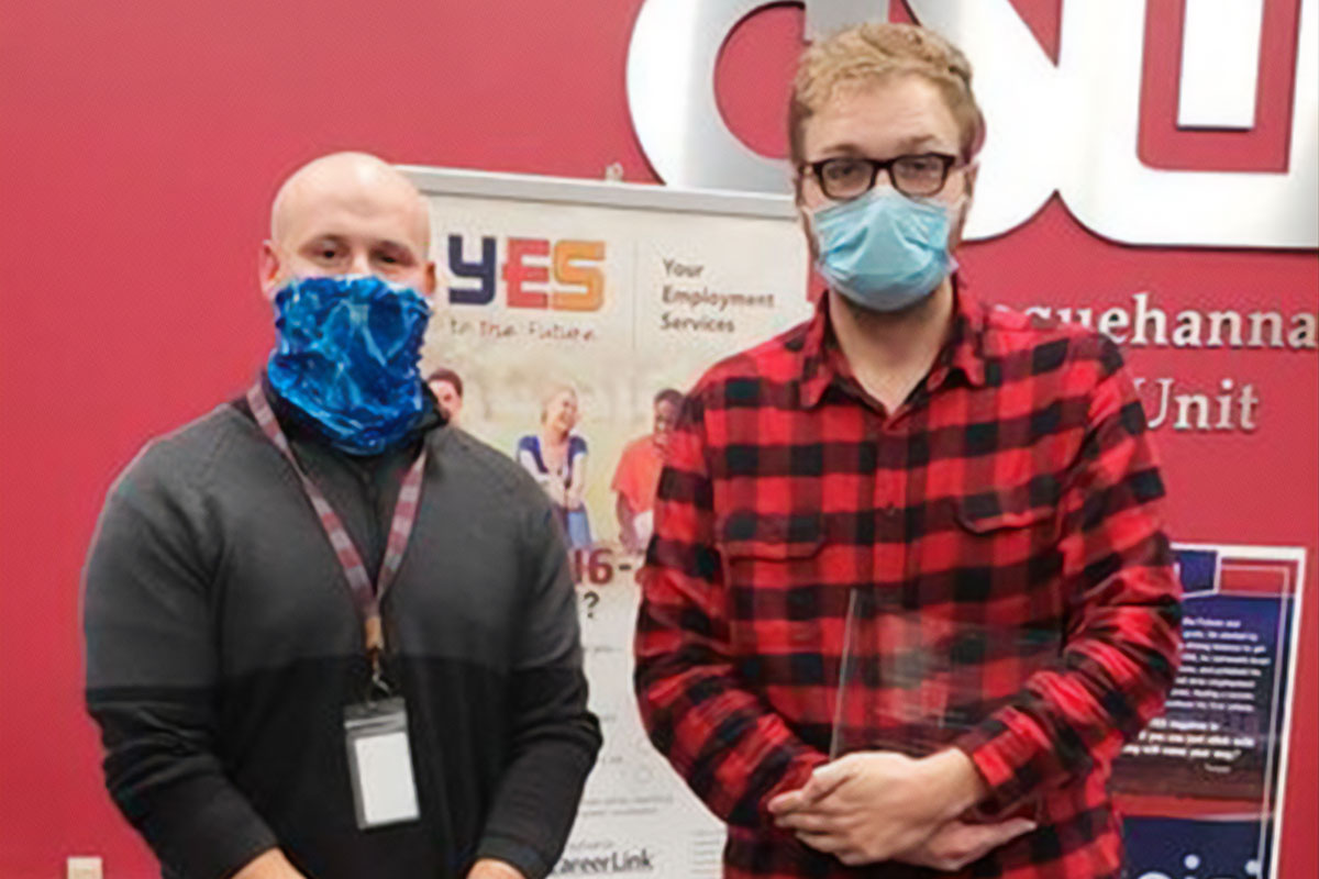 two men wearing face masks standing side by side