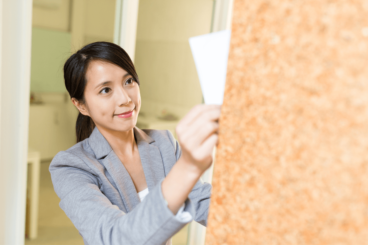 young Asian woman posting a piece of paper on the wall