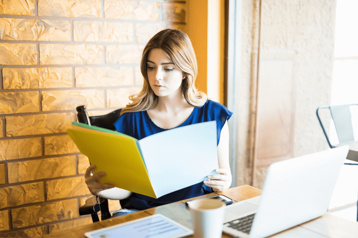 young woman looking at a file folder while sitting at a desk