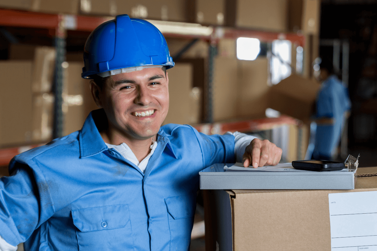 smiling man with hard hat and clipboard