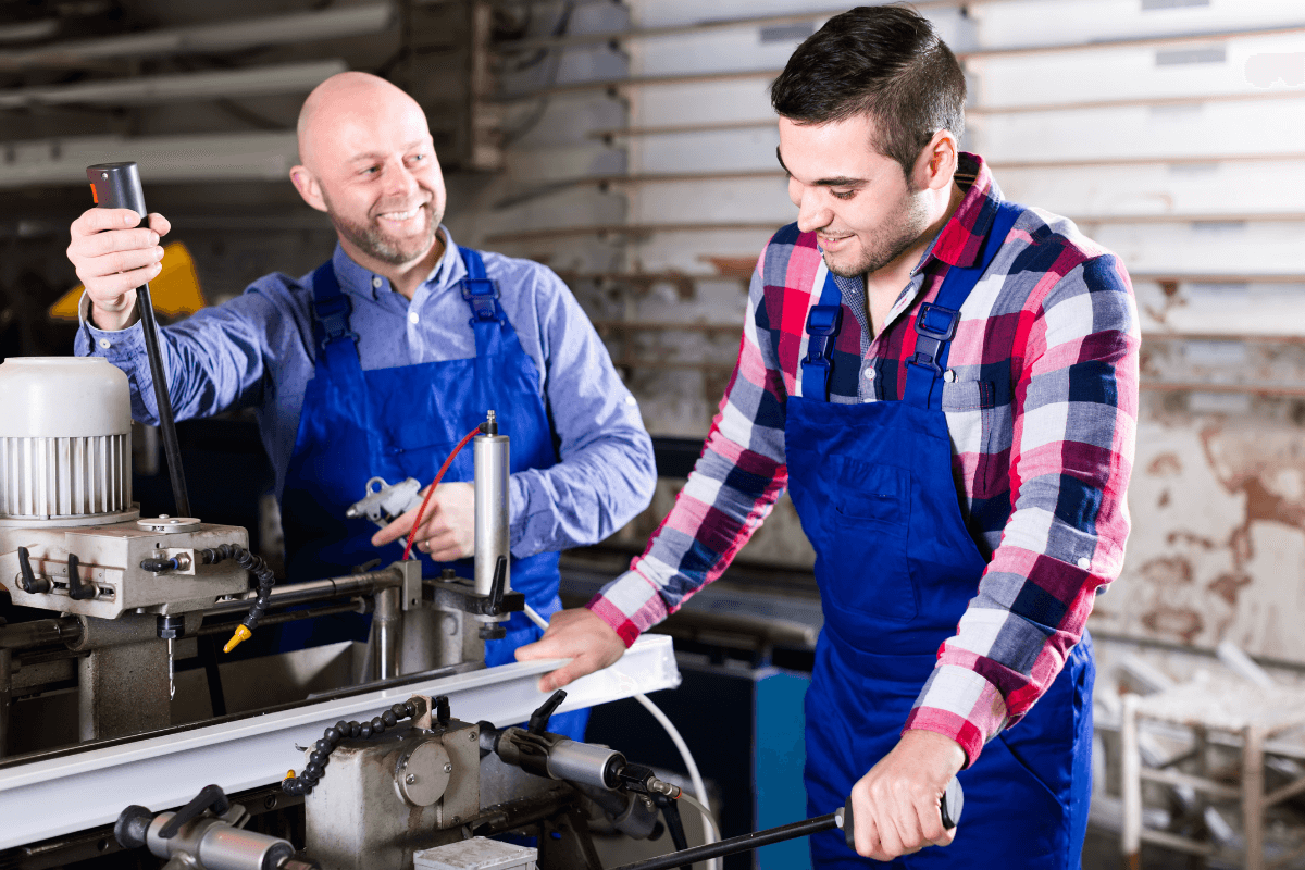 two men in work clothes at a manufacturing plant