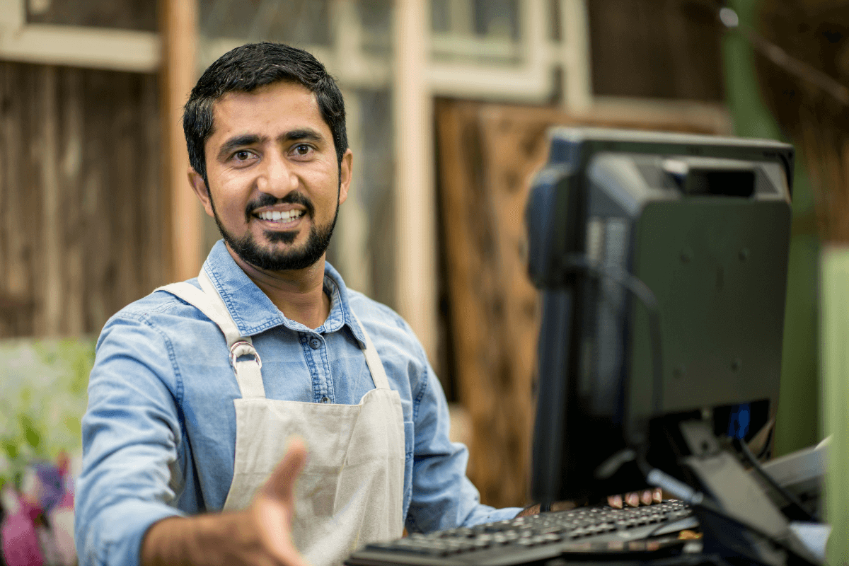 smiling man working the register at a store